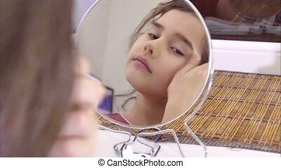teen girl indoor combing her hair before mirror