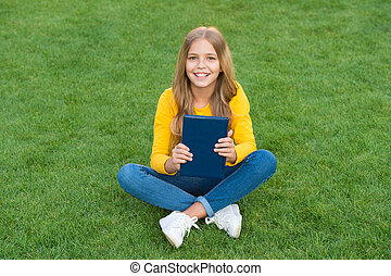 teen girl inspired with new book. relax on green grass. spring leisure time. happy childhood. kid read book outdoor in park. happy little girl study on holiday. kid beauty and fashion
