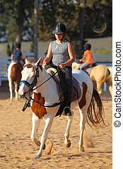 Teen girl is riding a horse