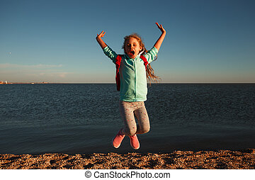 Teen girl jumping on the beach at sunset