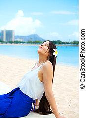 Teen girl leaning back on Hawaiian beach enjoying sun