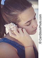 teen girl listen sea shell