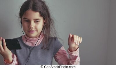 Teen girl listening to music headphones and dancing on a smartphone
