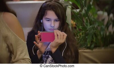 teen girl listening to music on smartphone sitting in fast food cafe. baby girl eating in a indoors cafe pizza