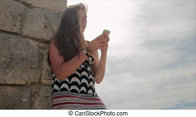 Teen girl listening to music with headphones on smartphone on a background of sea and the ruins of the ancient city