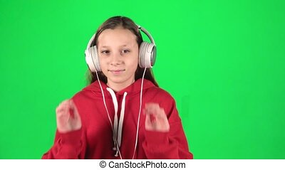 Teen girl listens to music and moving in large white headphones on green background. Slow motion