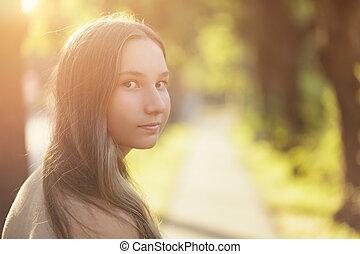 teen girl looking back on walk, summer time