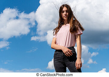Teen girl looking in camera and posing with sky at background