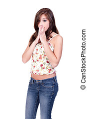 Young girl in jeans and flower print top, with a wide-eyed look and holding her hands to her mouth, appearing as if she has been shocked or embarrassed.