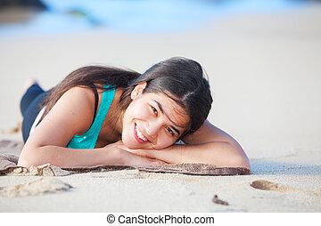 Teen girl lying down on sandy beach, head on arms