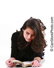Teen girl lying on floor reading Bible