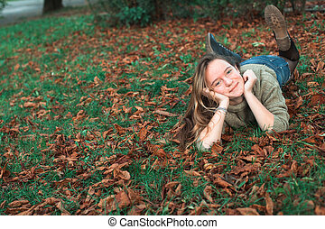 Teen girl lying on the fallen yellow leaves in autumn park.