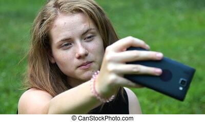 Teen girl making selfie with cellphone - Close-up shot of a...
