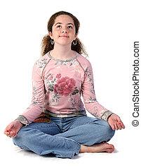 Teen Girl Meditating - A teenaged girl with her legs crossed...