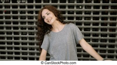 Teen girl moving funny in front of metal fence - Teen girl...