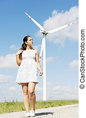 Teen girl next to wind turbine.