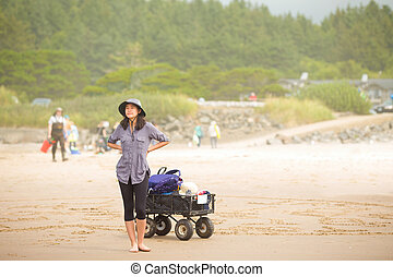 Teen girl on beach with wagon, looking out to sea