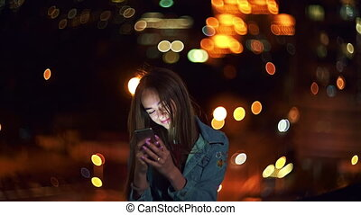 Teen girl on cityscape background holding a phone in hand chatting