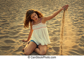 Teen girl on the beach playing with sand