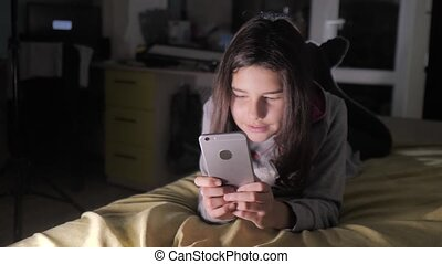 teen girl online shopping looks on her smartphone in bed...