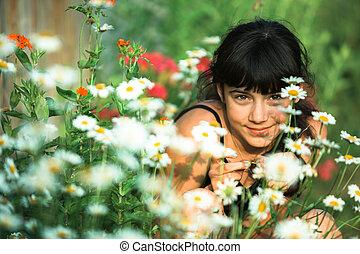 Teen girl outdoor among green wildflowers.