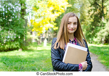 Teen girl outdoor holding books