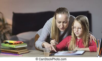 Teen girl painting with her mother at home