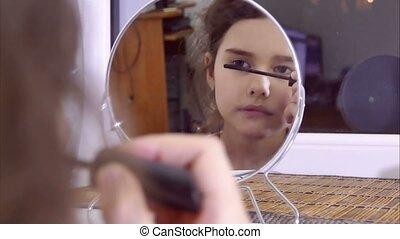 teen girl paints eyelashes before a mirror - teen girl...