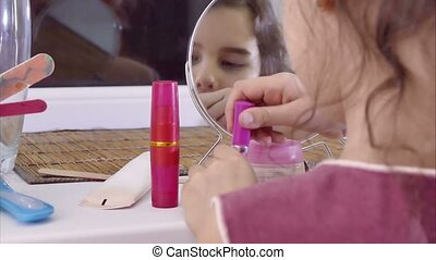teen girl paints lips before a mirror indoor - teen girl...