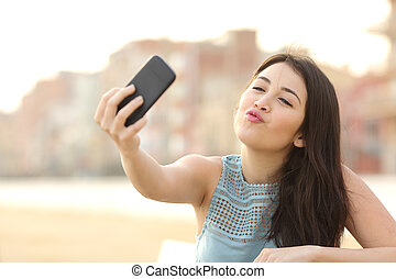 Teen girl photographing a selfie with a smart phone