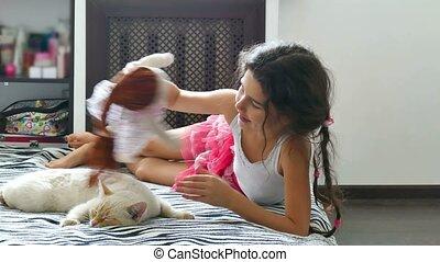 teen girl play with a doll cat sleeps next