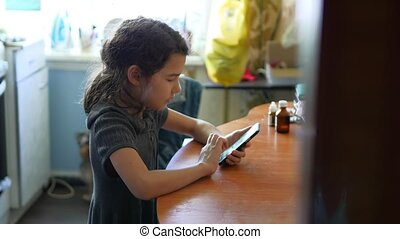 teen girl playing in the smart phone in the kitchen school girl online game