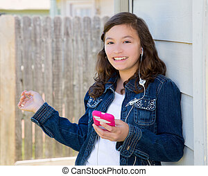 teen girl playing music with smartphone earbuds