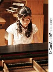 Teen girl playing piano