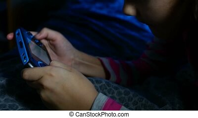 teen girl playing portable video online kid game a console...