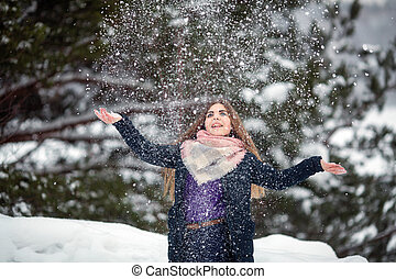 Teen girl playing with snow in the park at winter.