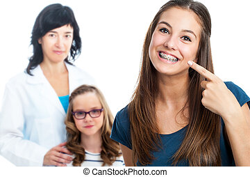 Teen girl pointing at dental barces with doctor in background.