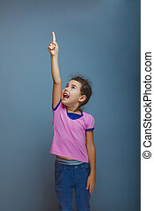 teen girl pointing at the sky on gray background