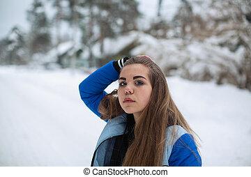 Teen girl portrait in the park in snowy winter.