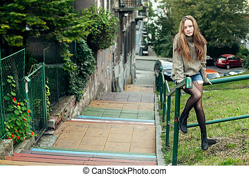 Teen girl poses for the camera in the little street.