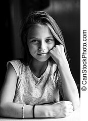 Teen girl posing for the camera sitting at the table. Black and white photography.