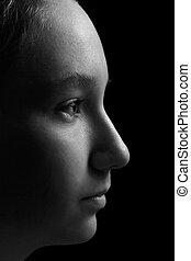 teen girl profile portrait on black background