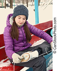 teen girl put on skate boots ice rink