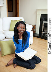 Teen girl reading a book in the liv