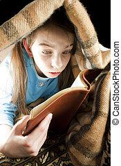 Teen girl reading book hiding under blanket