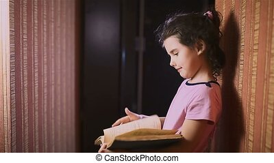 teen girl reading book is a wall indoor