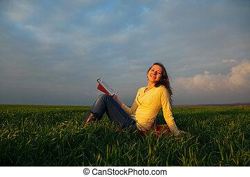 Teen girl reading book outdoors