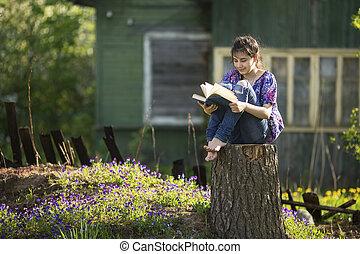 Teen girl reads book sitting