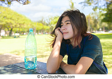 Teen girl resting chin on hand outdoors at picnic table