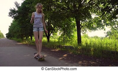 Teen girl riding skateboard in countryside - Teenager girl...